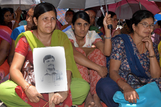 Sarmila Tripathi, 36, left, holds her missing husband Gyanendra Tripathi's portrait, as she along with others stages a sit- in protest in front of Nepal prime minister's residence in Katmandu, Nepal, Tuesday, June, 19, 2007. About 200 people barricaded the Nepalese prime minister's house Tuesday, demanding the government reveal the whereabouts of hundreds of people who allegedly disappeared during a decade-long civil conflict. (AP Photo/ Binod Joshi)